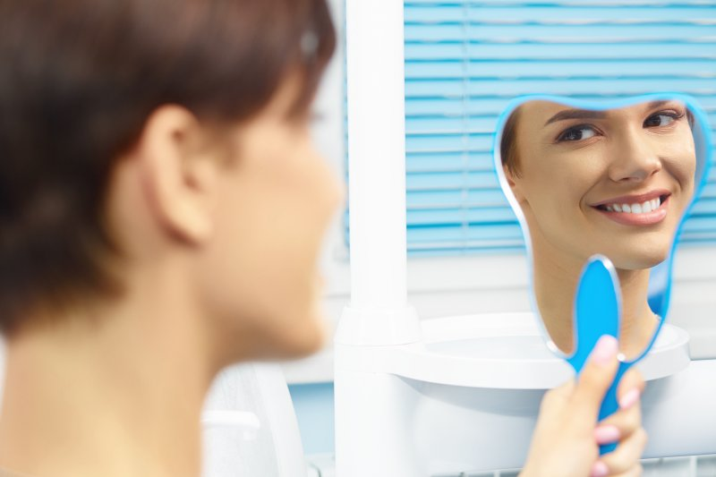 a woman smiling at herself in the mirror at the dentist office