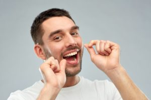 Happy man flossing healthy teeth
