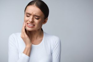 Woman with tooth pain in white shirt