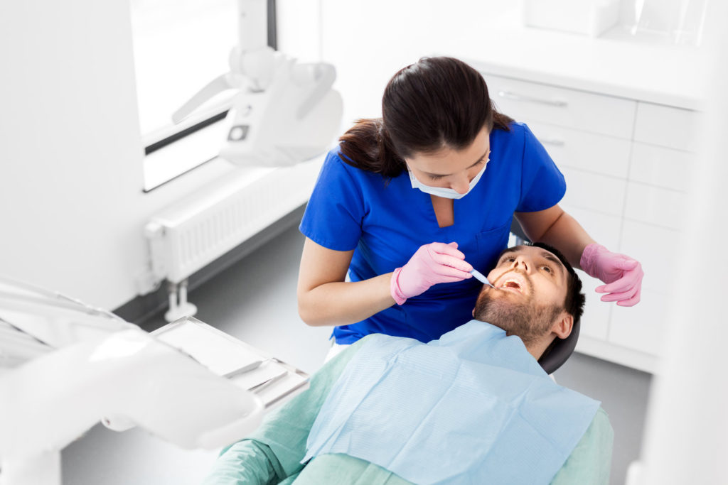 A dentist inspects a mouth for oral cancer