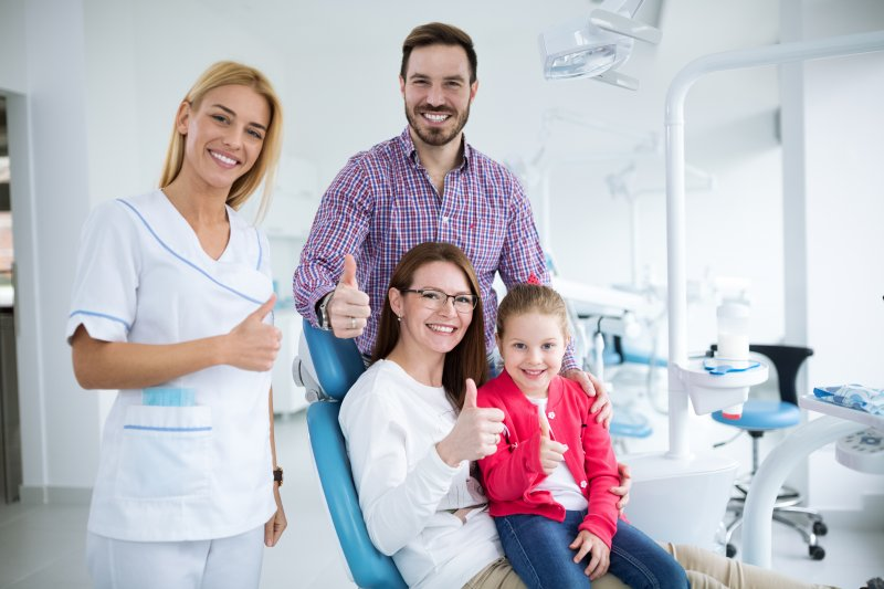 a husband, wife, and child giving a thumbs up while standing next to a family dentist