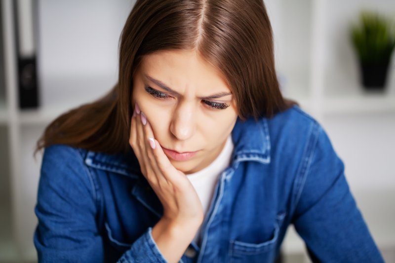 a young woman wearing a denim blouse and holding her cheek in pain because of a toothache