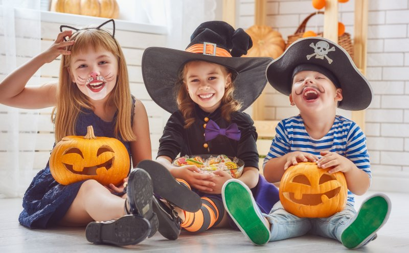 three small children all seated and holding pumpkins and Halloween candy