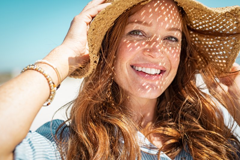 a young female wears a wide-brimmed hat while smiling on the beach