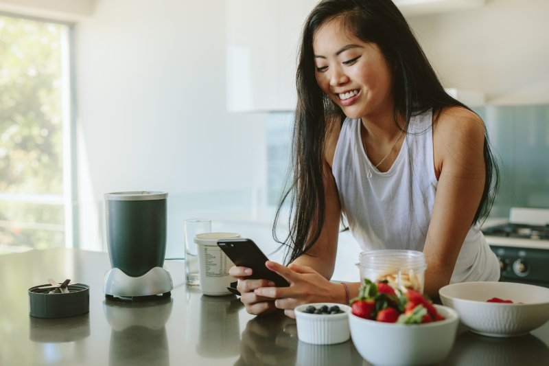 Woman smiling while looking up TikTok Recipe