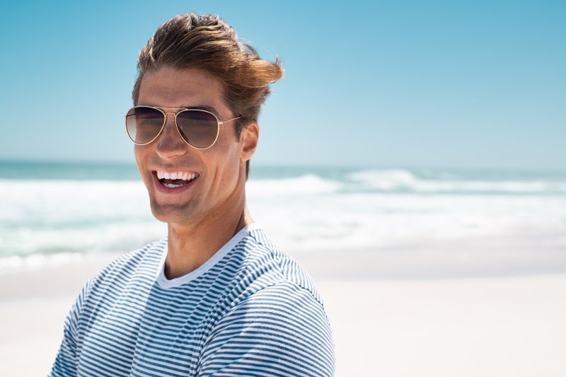 a man standing on the beach and smiling after taking steps to prevent dental emergencies in Rochester